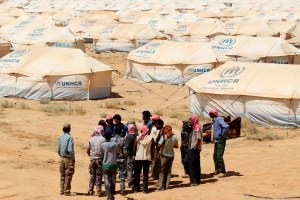 Jordanian workers take a UNHCR official on a walk around tents at the Zaatri refugee camp for Syrian refugees in Mafraq
